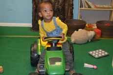 "Aria riding the tractor in the ""Farm"" room!"